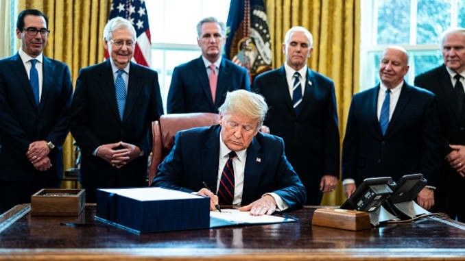 "Le président Donald Trump signe la proposition de loi de 2000 milliards ""H.R. 748, the CARES Act"" dans le Bureau Ovale de la Maison Blanche le 27/03/2020. Source: Erin Schaff 